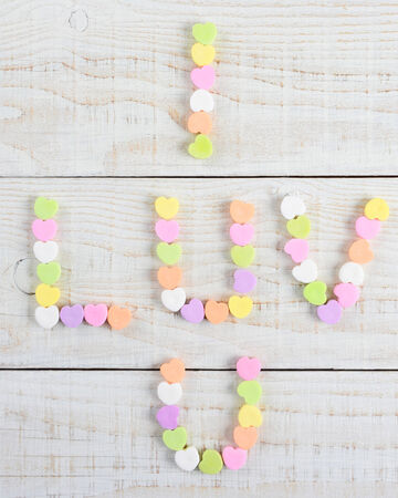high angle shot: High angle shot of a group of pastel candy Valentines hearts forming I Luv U on a rustic white wood table.