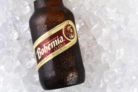 international beer: IRVINE, CA - JANUARY 12, 2015: A bottle of Bohemia beer on a bed of ice closeup. From Cerveceria Cuauhtemoc-Moctezuma, founded in 1890, now a subsidiary of Heineken International. Editorial