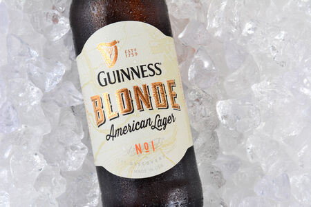 producing: IRVINE, CA - JANUARY 12, 2015: A bottle of Guinness Blonde American Lager on a bed of ice.  Guinness has been producing beer in Ireland since 1759.