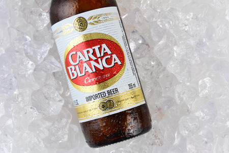 international beer: IRVINE, CA - JANUARY 11, 2015: A bottle of Carta Blanca Beer, closeup on a bed of ice. From Cerveceria Cuauhtemoc-Moctezuma, founded in 1890, now a subsidiary of Heineken International. Editorial