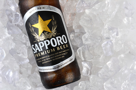 sapporo: IRVINE, CA - JANUARY 12, 2015: A bottle of Sapporo Beer closeup on a bed of ice. The Japanese brewery was founded in 1876 by German trained brewer Seibei Nakagawa. It is the oldest beer brand in Japan.