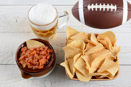 corn chips: High angle shot of a bowl of corn chips a crock full of fresh salsa a mug of beer and an American football on a whitewashed rustic wood table. Horizontal format.
