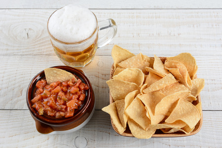corn chips: High angle shot of a bowl of corn chips a crock full of fresh salsa and mug of beer on a whitewashed rustic wood table. Horizontal format. Stock Photo