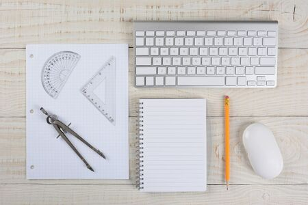 Overhead shot of a computer keyboard and mouse next to a sheet of graph paper, a compass and protractor, on a whitewashed wood table, in a home office.
