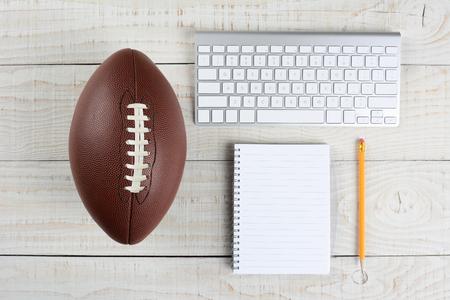 Progetto ancora in vita Fantasy Football. Tastiera di un computer, carta e penna e di un calcio in stile americano su un tavolo di legno bianco in un ufficio in casa. Archivio Fotografico - 35715103