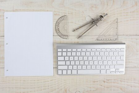 telecommute: High angle shot of a computer keyboard next to a sheet of graph paper, a compass and protractor, on a whitewashed wood table, in a home office. Stock Photo