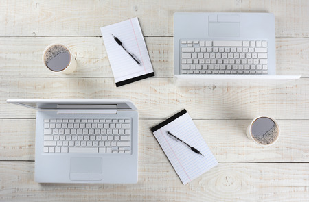 work station: High angle shot of two computer work stations back-to-back with almost identical layouts. Horizontal format on a whitewashed wood table. Stock Photo