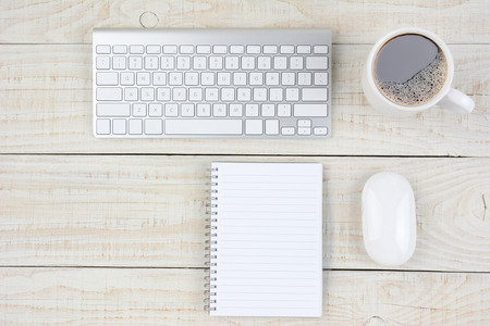 Overhead shot of a rustic white wood desk with keyboard, mouse, note pad, and coffee cup. Horizontal format with copy space.