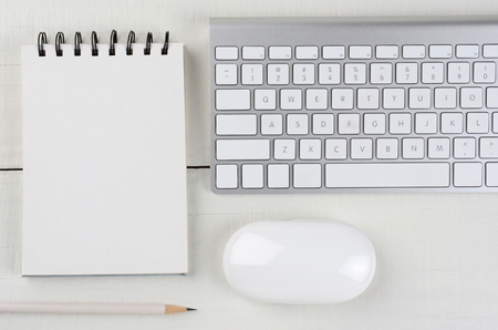 home office desk: Horizontal image of a white wood home office desk with a computer keyboard, blank note pad, a white pencil, and mouse. A monochromatic still life shot from a high angle. Stock Photo