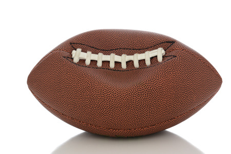 football: Closeup of an Professional American style football partially deflated on white with reflection.
