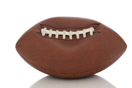 Gros plan d'un ballon de football de style américain professionnel partiellement dégonflé sur blanc avec la réflexion. Banque d'images - 35967296