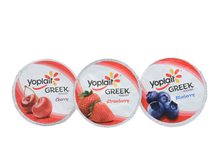IRVINE, CA - SEPTEMBER 15, 2014: Three different containers of Yoplait Greek Yogurt isolated on white. In 1965, two French dairy co-operatives, Yola and Coplait, merged, becoming Yoplait.