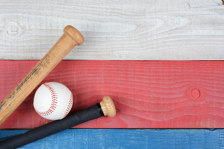 inbetween: High angle shot of a baseball and bats on a red, white and blue picnic table. Horizontal format with copy space. Suitable for American Holidays: 4th of July and Memorial Day,