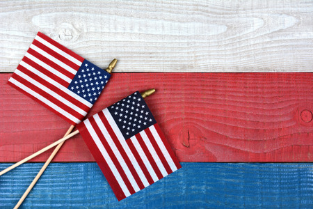 High angle shot of two crossed American flags on a red, white and blue picnic table. Horizontal format with copy space. Stock Photo