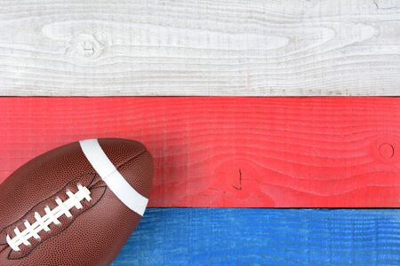 high angle shot: High angle shot of an American style football on a red, white and blue picnic table. Horizontal format with copy space. Suitable for American Holiday: 4th of July and Memorial Day, Stock Photo