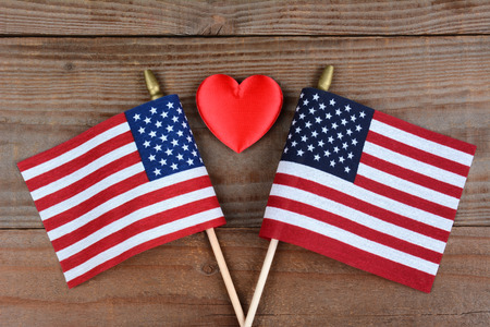 High angle shot of two crossed American flags on a rustic wood surface with a red heart in.between. Horizontal format.