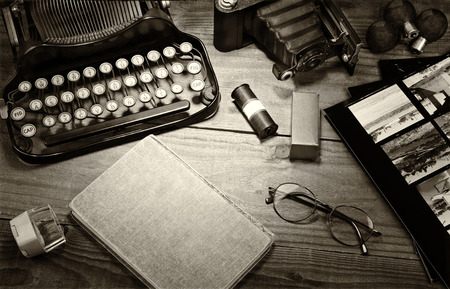 Closeup of a vintage photography still life with typewriter, folding camera, loupe, roll film, flash bulbs, contact prints and book on a wood table. Black and white toned image for a vintage feel. Foto de archivo