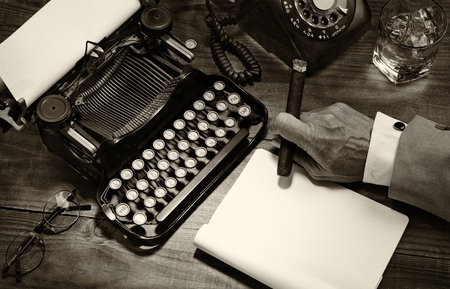Closeup of a writer at his desk with a typewriter, rotary telephone, glass of whiskey and a cigar. Black and white toned image for a vintage feel. Only the mans hand holding a cigar is shown. Stock Photo