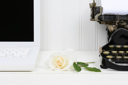 Closeup of a white desk with a rose laying between a modern laptop computer and an antique typewriter. Only half of the laptop and typewriter are shown. Horizontal format. photo