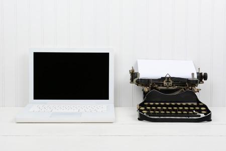 Close up de uma mesa branca com um computador laptop moderno e uma máquina de escrever antiga. Formato horizontal com espaço da cópia. Old vs novo conceito.