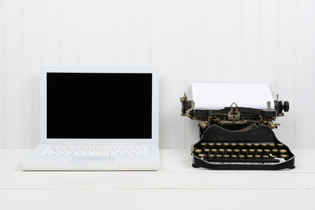 Closeup of a white desk with a modern laptop computer and an antique typewriter. Horizontal format with copy space. Old vs new concept.