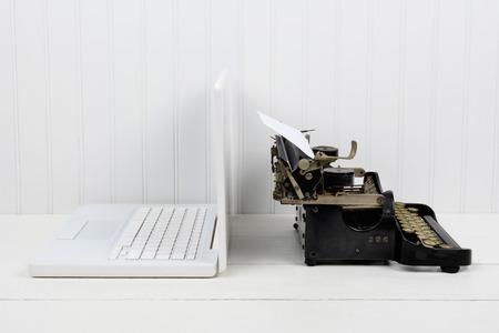 현대 노트북 컴퓨터와 다시 다시 골동품 타자기 흰색 책상의 근접 촬영입니다. 복사 공간 가로 형식입니다. 새로운 개념의 대 이전.
