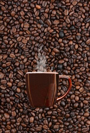 A mug of steaming hot coffee on a background of fresh roasted beans. Vertical format with copy space. photo