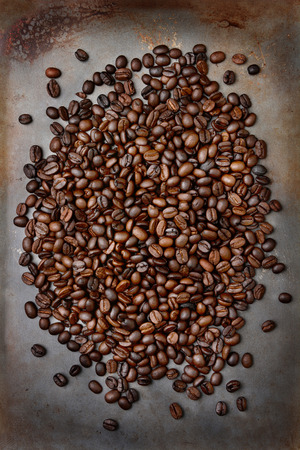 high angle shot: High angle shot of fresh roasted coffee beans ion a metal baking sheet. Vertical format.