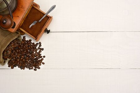 coffee table: High angle shot of a bag of coffee beans and an antique  grinder on a rustic white wood table. The items are in the upper left corner leaving room for your copy.