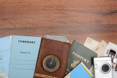 high angle shot: High angle shot of a travel still life. Items include: passport, wallet, post cards, camera, pictures, maps, and itinerary folder on a wood desk. Horizontal format with copy space at the top. Stock Photo