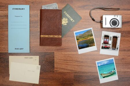 post cards: High angle shot of a passport, wallet, post cards, camera, pictures, and itinerary folder on a wood desk. Horizontal format with copy space in the middle. Photos could easily replaced with yours.