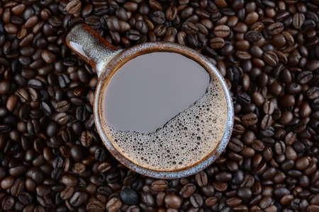 high angle shot: High angle shot of a coffee mug surrounded by fresh roasted beans.
