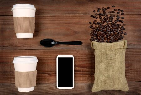 high angle shot: high angle shot of take-out coffee cups and a burlap bag with beans spilling out on a rustic wood table. A cell phone and spoon in the middle with copy space, Horizontal Format.