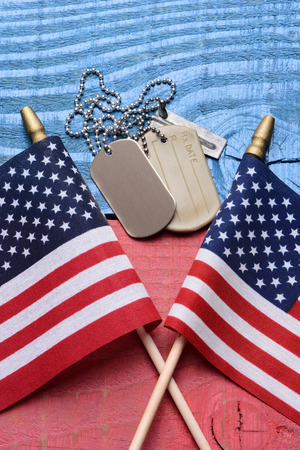 Overhead shot of a set of dog tags and two American flags on a red white blue patriotic table. Vertical format. Useful for 4th of July, Memorial Day and Veterans Day projects. Stock Photo