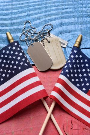 dog days: Tiro de arriba de un conjunto de placas de identificación y dos banderas de Estados Unidos en un azul blanco rojo patriótico mesa. Formato vertical. Útil para el 4 de julio, Memorial Day y proyectos del Día de los Veteranos.