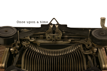 An old fashioned typewriter with the words Once upon a time. Closeup of the antique machines ribbon and carriage. With warm vintage tones. photo