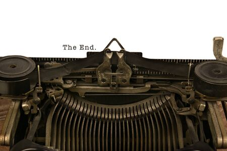 An old fashioned typewriter with the Words The End. Closeup of the antique machines ribbon and carriage. With warm vintage tones. photo