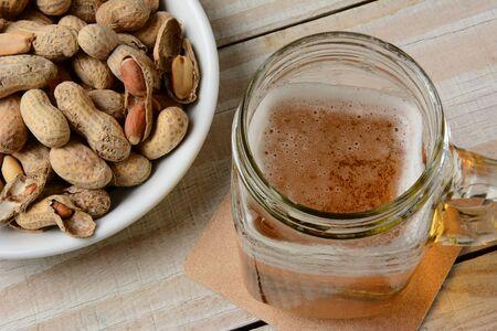 jarra de cerveza: Alto �ngulo de disparo de una cerveza en un estilo de cristal frasco de conservas junto a un cuenco de cacahuetes.
