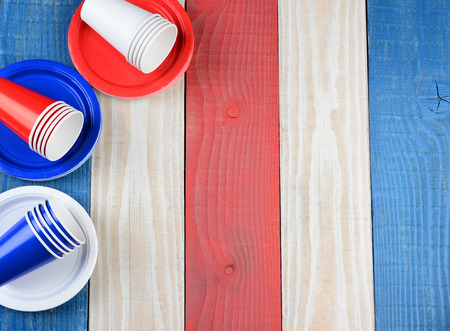 july 4th fourth: High angle shot of a red, white and blue picnic table with matching plates and cups. The cups and plates are set ot one side leaving copy space.