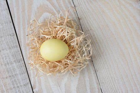 raffia: Overhead shot of a yellow dyed Easter Egg in a nest made of raffia on a rustic white wooden kitchen table. Horizontal format. Stock Photo