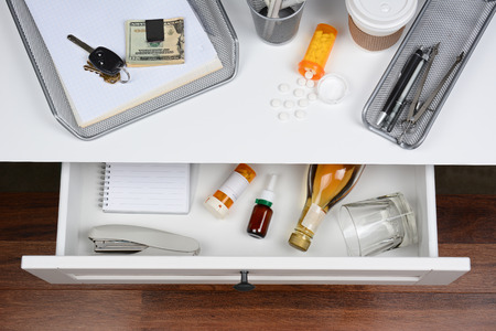 High angle shot of an open desk drawer showing the items inside. The top of the desk has a coffee cup, spilled prescription bottle, in-box, car keys and money clip.
