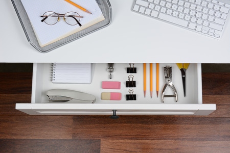 High angle shot of an open desk drawer showing the items inside. The top of the desk has a computer keyboard and wire in-box with paper and pencil. The drawer has pencils, erasers, stapler and more. Archivio Fotografico