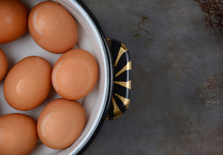 overhead shot: Overhead shot of brown eggs in pot of water Stock Photo