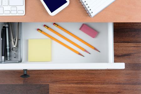 Tiro alto angolo di un cassetto della scrivania aperta mostrando gli oggetti all'interno. La parte superiore della scrivania ha una tastiera di un computer telefono cellulare e blocco note. Il cassetto pulito ha matite carta e organizzatore. Archivio Fotografico - 37601150