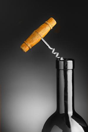 cork   screw: Old cork screw in blue wine bottle over a gray light to dark background. Stock Photo