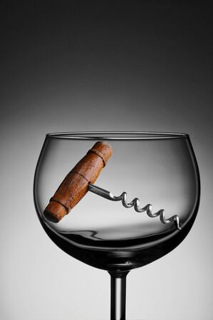 cork screw: An antique cork screw in a wine glass against a light to dark gray background. Stock Photo