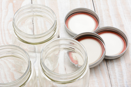 lids: Closeup of three glass canning jars on a rustic wood farmhouse style kitchen table. The lids are laying in the background. Shallow depth of field with focus on the jar rims.