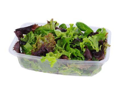 Fresh salad greens in a plastic tub.