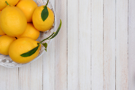 high angle shot: High angle shot of a basket of fresh picked lemons in the corner of the frame. Horizontal format with copy space. Stock Photo