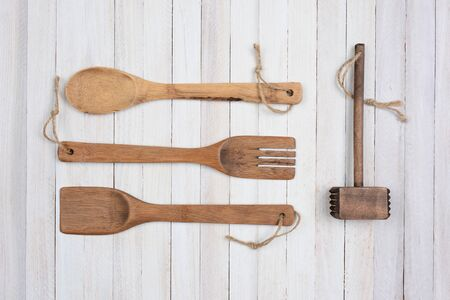 Overhead shot of four wooden kitchen utensils on a rustic white wood table. Items are: spoon, fork, spatula, and a mallet.